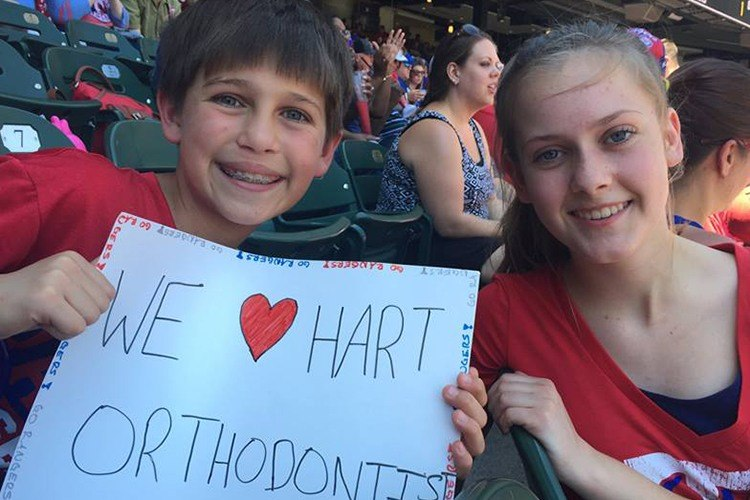 Kids at baseball game holding a we love hart orthodontics sign