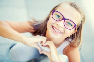 Girl with braces smiles during National Children's Dental Health Month
