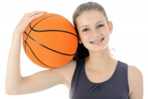 Smiling girl with basketball playing sports with braces